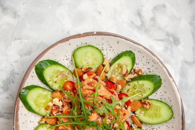 Mezzo colpo di sana e deliziosa insalata vegana fatta in casa decorata con cetrioli tritati in una ciotola su una superficie bianca macchiata con spazio libero