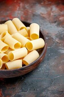 Половина снимка крупным планом сырых макарон в коричневом горшочке на черном столе