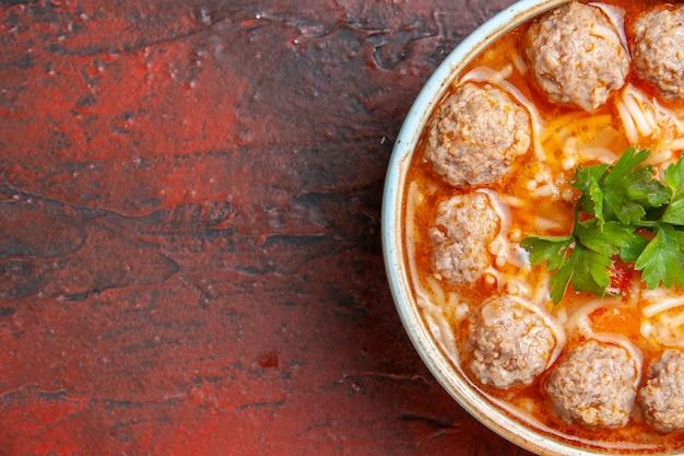 Mezzo colpo di zuppa di polpette con noodles in una ciotola marrone sul lato sinistro dello sfondo scuro