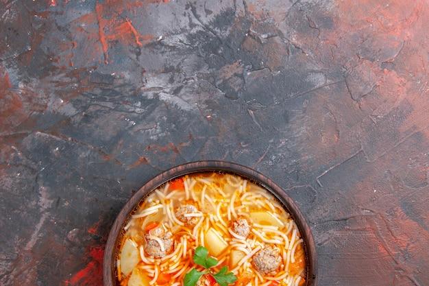 Mezzo colpo di zuppa di noodle con pollo in una ciotola marrone su sfondo scuro