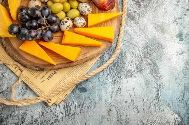 古い新聞の木製の茶色のトレイロープにさまざまな果物や食べ物と一緒に最高のスナックのハーフショット