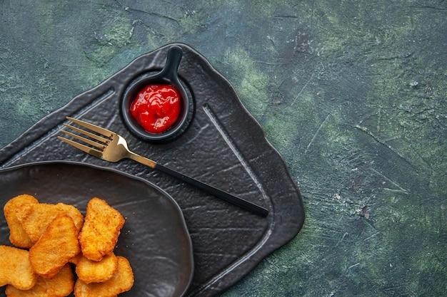 黒い皿にチキンナゲットのハーフショット、ダークカラーのトレイにフォークケチャップ