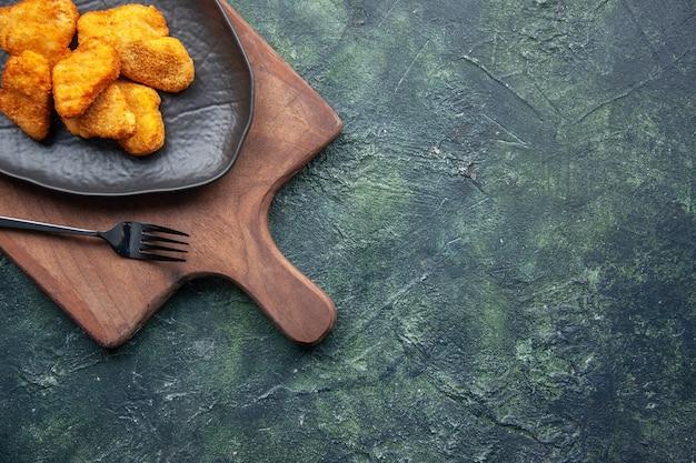 검은 접시에 치킨 너겟의 절반 샷과 여유 공간이있는 어두운 표면의 오른쪽에 나무 커팅 보드에 포크