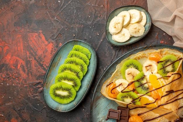 혼합 색상의 파란색 접시에 초콜릿 소스로 장식된 맛있는 크레이프에 감귤류 과일 반 샷