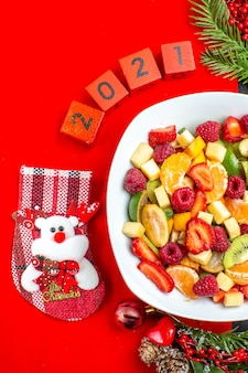 Половина выстрела коллекции свежих фруктов на тарелке украшения аксессуары еловые ветки и числа и рождественский носок на красной салфетке