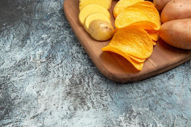 회색 테이블에 나무 커팅 보드에 바삭한 칩과 생 쌀된 감자의 절반 샷