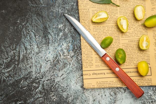 회색 배경에 신문에 신선한 금귤과 칼을 반으로 자른 반 샷