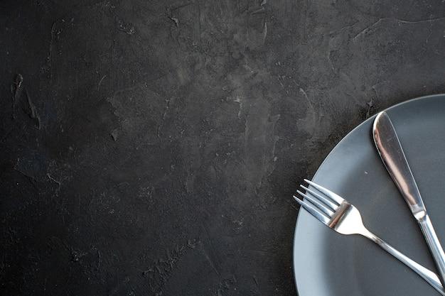 Половина набора столовых приборов на черной тарелке слева на темном фоне со свободным пространством