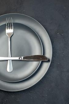 검은색 바탕에 여유 공간이 있는 두 가지 크기의 어두운 색 빈 접시에 설정된 칼 붙이 반 샷