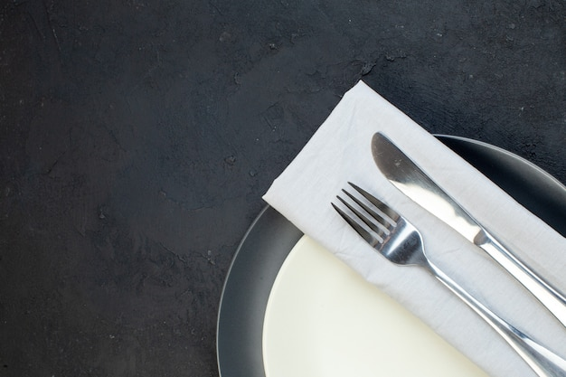暗い色の白いナプキンと黒い背景の異なるサイズの白い空のプレートに設定されたカトラリーのハーフショット