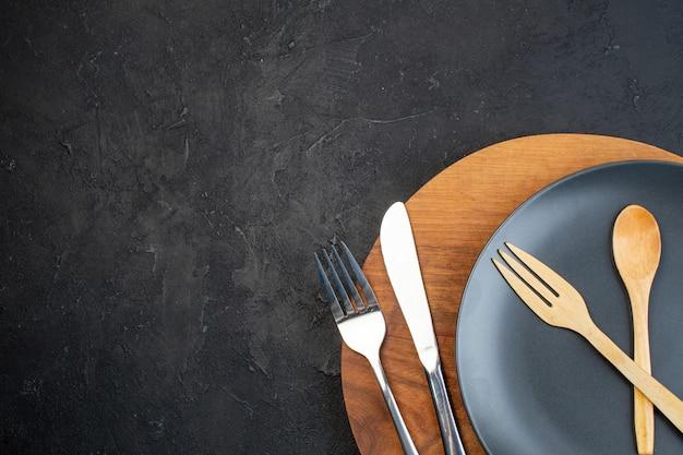 Половина выстрела темной тарелки и наборов столовых приборов из нержавеющей стали на коричневой круглой разделочной доске на черном фоне со свободным пространством