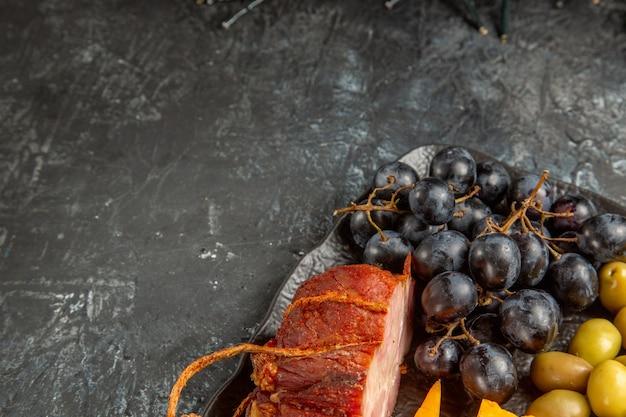 灰色の背景に茶色のトレイで提供されるワインのためのおいしい最高のスナックのハーフショット