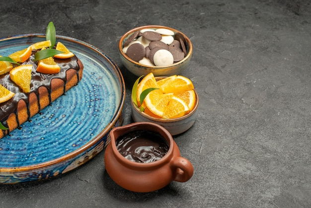 暗いテーブルの上に他のクッキーとオレンジとチョコレートで飾られたおいしいケーキのハーフショット