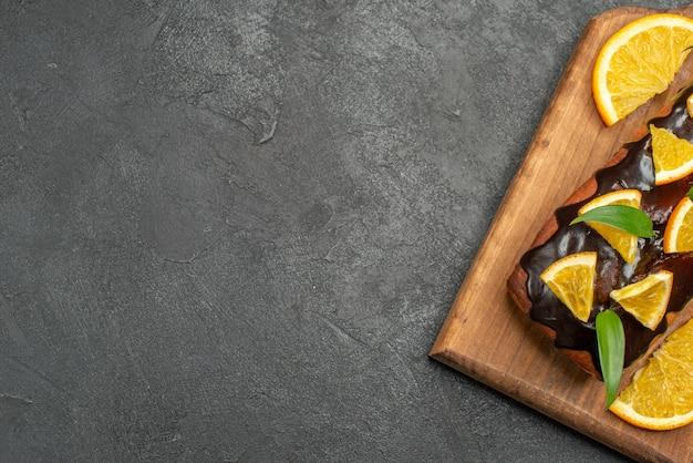 黒いテーブルのまな板にレモンとチョコレートで飾られたおいしいケーキのハーフショット
