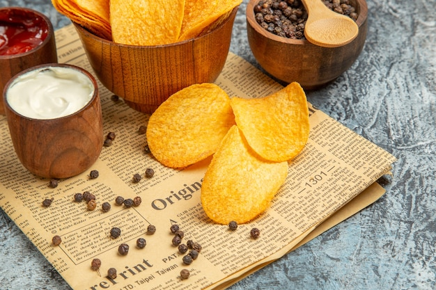 맛있는 수제 칩과 후추 그릇 마요네즈 케첩과 회색 테이블에 신문에 숟가락으로 소스의 절반 샷