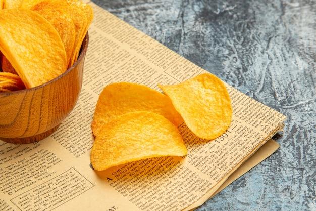 Половина выстрела вкусных домашних чипсов на газете на сером столе