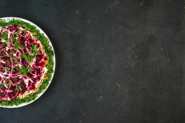 空きスペースのある黒い背景の右側にある白いプレートに緑で飾られたおいしいサラダのハーフショット
