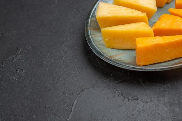 검은 배경에 왼쪽에 접시에 맛있는 슬라이스 치즈의 절반 샷