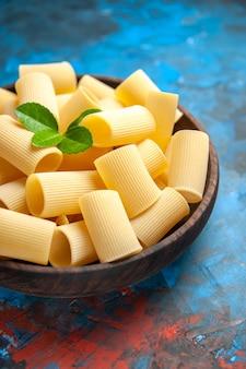 青の背景に茶色の鍋に緑のパスタ ヌードルを使った夕食の準備のハーフ ショット