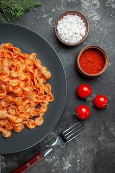 黒い皿に夕食用の簡単なパスタのハーフショットと、暗いテーブルの上のさまざまなスパイスとトマトのフォーク