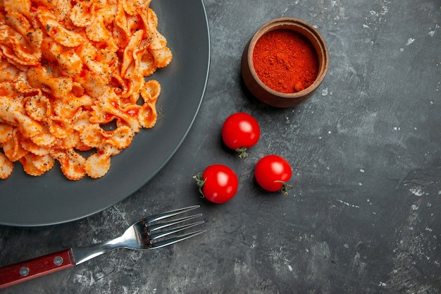 暗い背景に黒い皿とフォーク ペッパーとトマトの夕食用の簡単なパスタのハーフ ショット