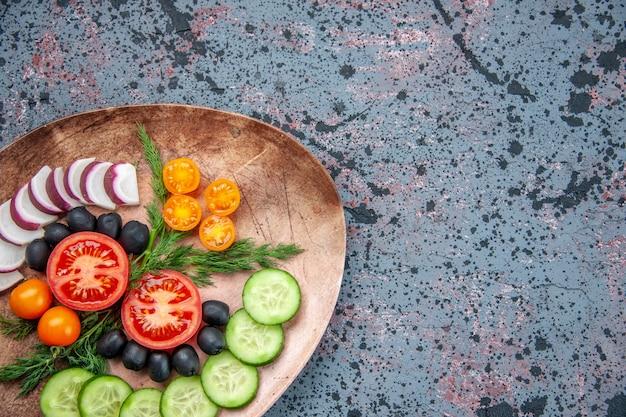 혼합 색상 배경에 오른쪽에 갈색 접시에 신선한 다진 야채의 절반 샷
