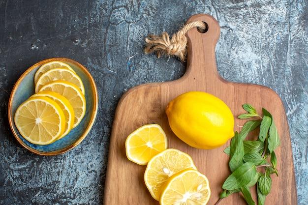 어두운 배경에 나무 커팅 보드에 신선한 레몬과 민트 나이프의 절반 샷