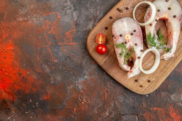 ミックスカラーの表面の左側にある新鮮な生の魚とペッパーオニオングリーンのトマトのハーフショット