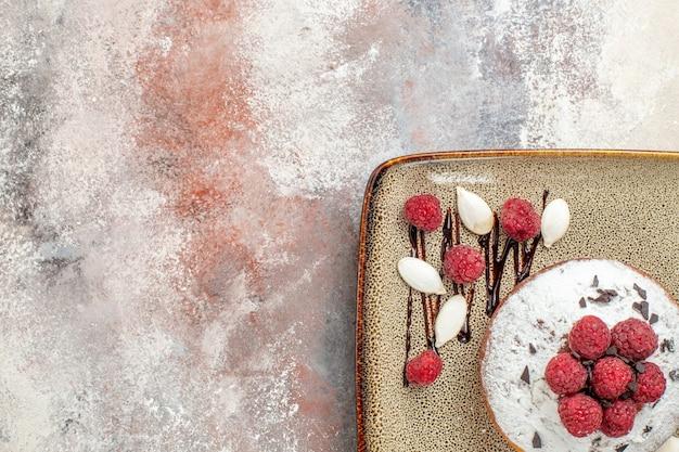 混合色のテーブルの上の白いトレイの赤ちゃんのためのラズベリーと焼きたてのケーキのハーフショット