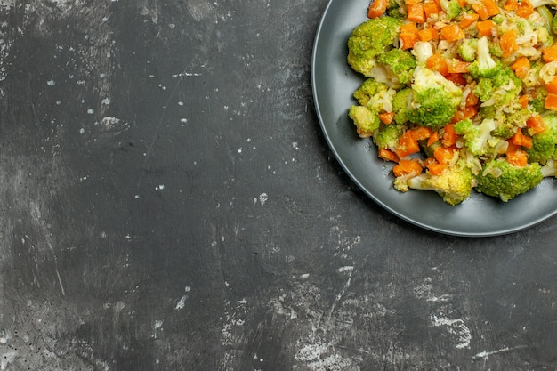 Половина здорового обеда с брокколи и морковью на черной тарелке на сером столе