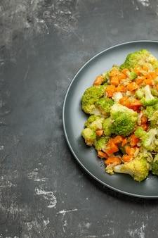 회색 테이블에 검은 접시에 브로콜리와 당근으로 건강한 식사의 절반 샷