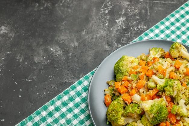 灰色のテーブルの上の緑のストリップタオルで健康的な野菜サラダのハーフショット