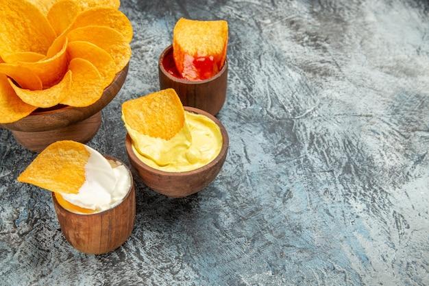 회색 테이블에 만든 바삭한 감자 칩 케첩 마요네즈 소스의 절반 샷