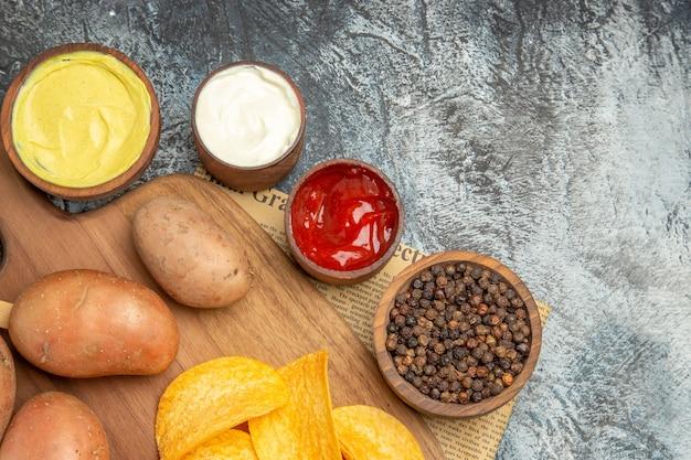 신문에 나무 커팅 보드 고추 케첩 소스 마요네즈에 집에서 만든 맛있는 감자 칩의 절반 샷