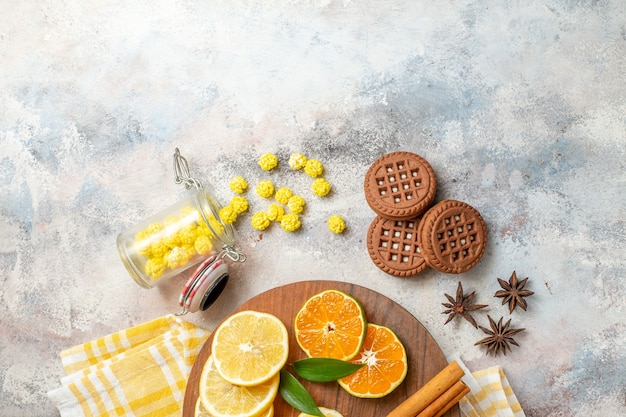 나무 커팅 보드에 레몬 슬라이스 계피 라임과 흰색 테이블에 비스킷의 절반 샷