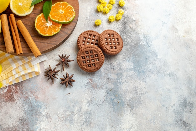 Половина выстрела из ломтиков лимона, корицы, лайма на деревянной разделочной доске и печенья на белом столе