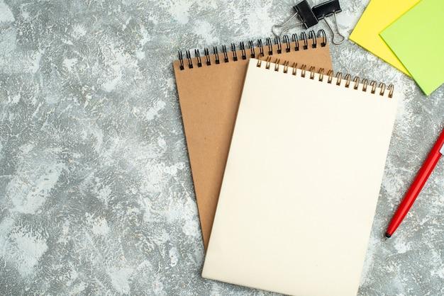 氷の背景にペンカラフルなメモ用紙と2つのクラフトスパイラルノートのハーフショット