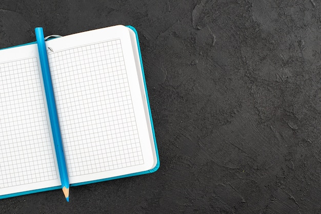 열린 파란색 노트북과 펜의 절반 샷
