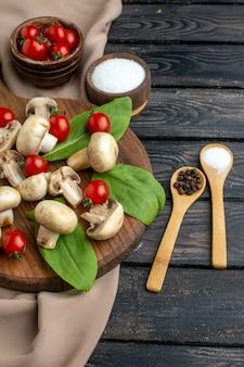 黒の背景に木の板タオルに生の新鮮なキノコとトマトのスパイスのハーフショット