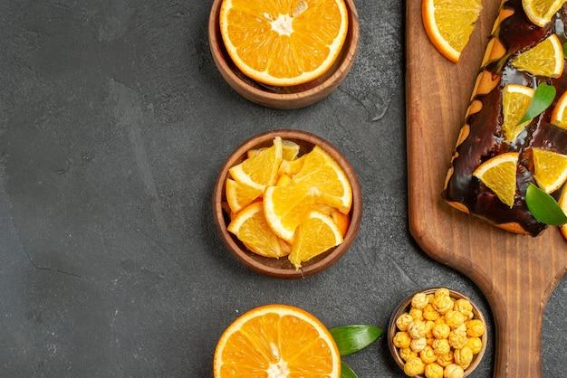 Половина выстрела набора, разрезанного пополам, нарезанного кусочками свежих апельсинов и мягких пирожных на черном столе