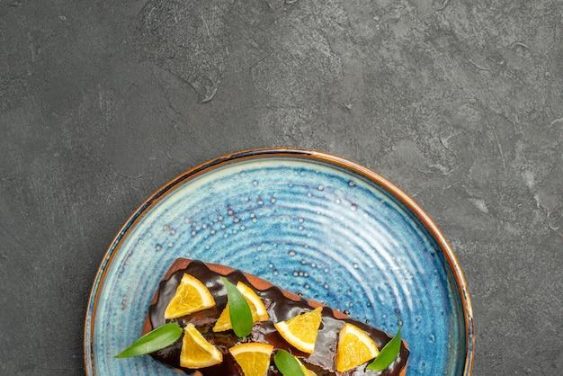 暗いテーブルにレモンとチョコレートで飾られた柔らかいケーキのハーフショット