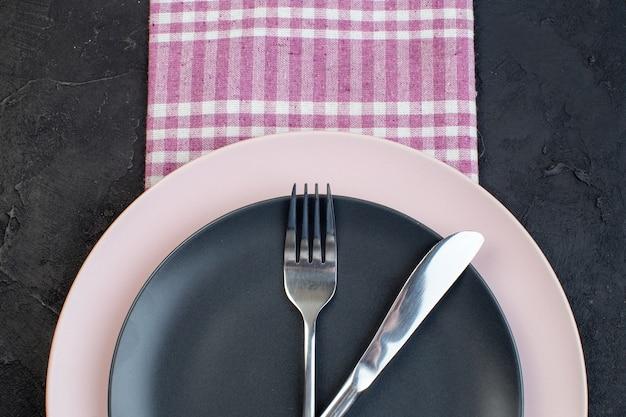 여유 공간이 있는 검정색 배경에 분홍색 벗겨진 수건에 있는 다채로운 세라믹 빈 접시에 설정된 스테인리스 칼 붙이 반 샷