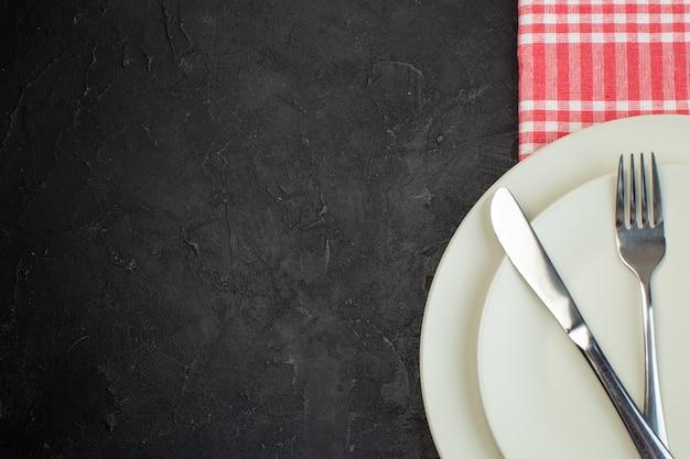 여유 공간이 있는 검정색 배경의 왼쪽에 있는 빨간색 벗겨진 수건에 흰색 빈 접시에 놓인 스테인리스 수저의 절반