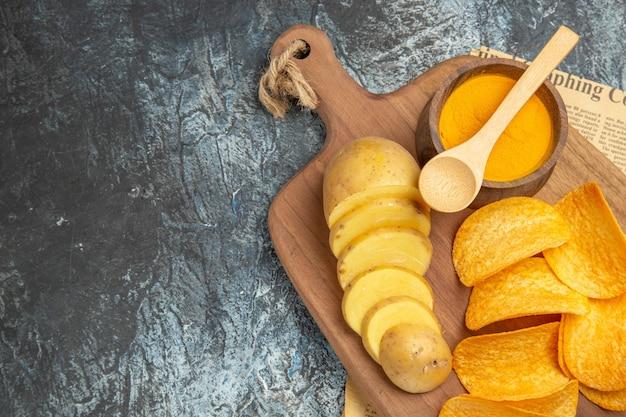 Половина выстрела вкусных домашних чипсов, нарезанных ломтиками картофеля на деревянной разделочной доске, на газете на сером столе