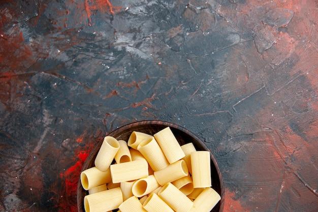 黒いテーブルの鍋の中の未調理のパスタのハーフショット