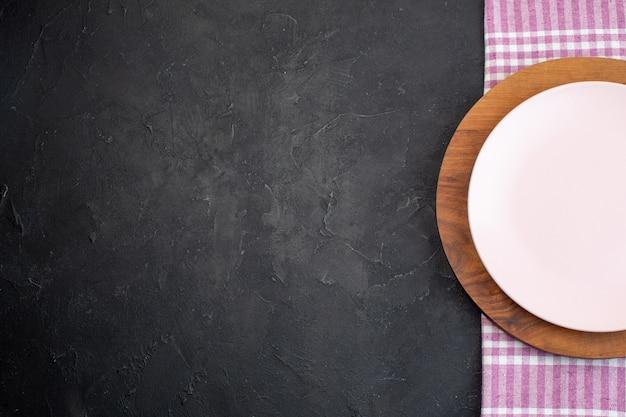 Половина выстрела белых и коричневых керамических пустых тарелок на черном фоне со свободным пространством