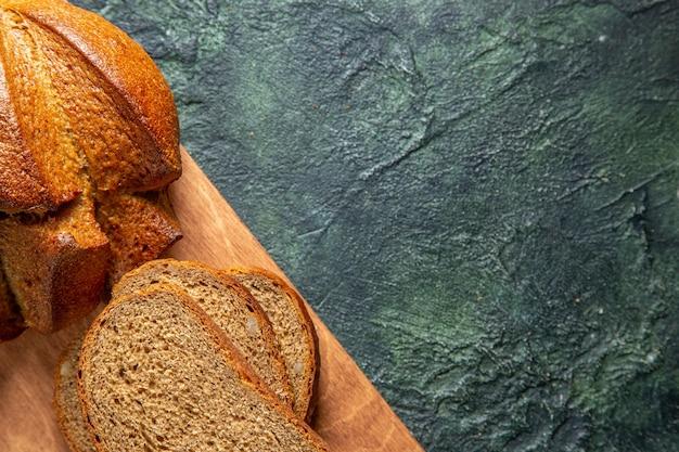 Половина выстрела целого и нарезанного черного хлеба на коричневой деревянной разделочной доске на фоне темных цветов