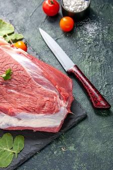 Mezza ripresa di carne rossa fresca cruda e verdure su taglieri di pomodori a coltello su sfondo nero verde di colori misti