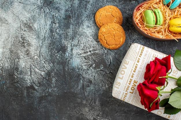Mezzo colpo di rosa rossa su una bellissima confezione regalo con deliziosi macarons e biscotti su sfondo scuro ghiacciato