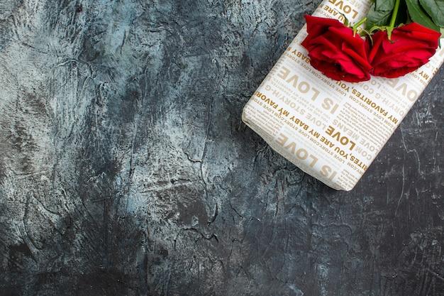Mezzo colpo di rose rosse su una bellissima confezione regalo su sfondo scuro ghiacciato con spazio libero